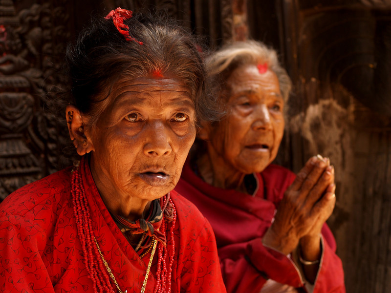 Two old women seated in the entrance of a temple waiting a tip from tourist.