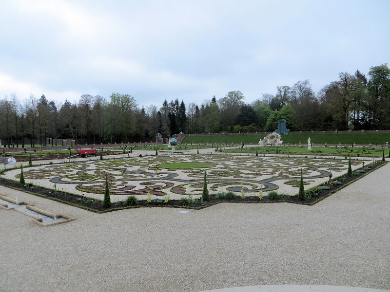 "This part of the garden (the ""Lower Garden"") is laid out in eight ""parterres,"" which seems to mean square pieces of land forming a symmetrical pattern and interspersed with  walkways.  The outer parterres are grassy and the four inner parterres are planted as ""parterres de broderie"" (broderie being the French word for embroidery).  Hence the elaborate curlicue patterns.  When the garden was originally built, simultaneously with the building of the palace, 6,000 soldiers were seconded to dig the ground.  Willem III liked to collect unusual and exotic plants and made use of his connections with the East and West Indies Company to obtain specimens."