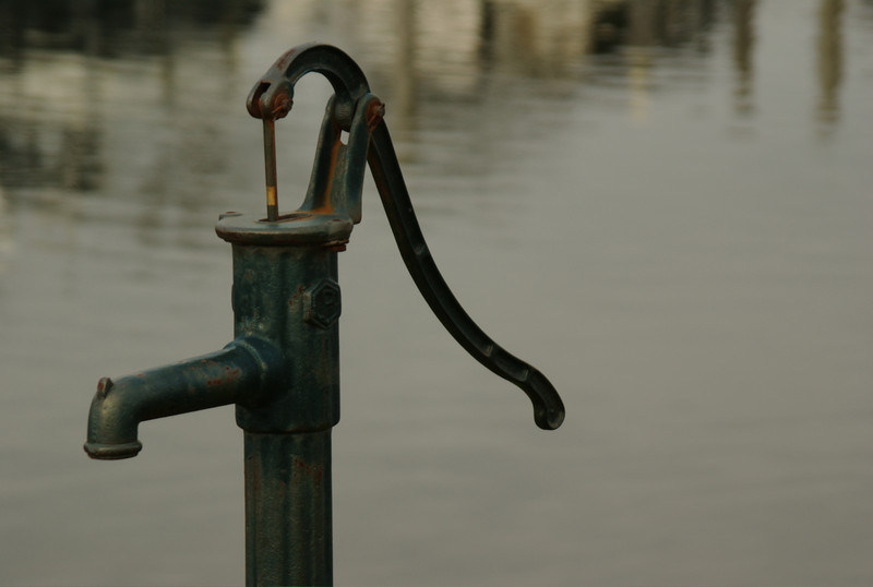 An old fashioned water pump next to the river in Roermond, The Netherlands.