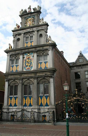 """Westfries Museum. The top of the building proudly displays the family shield of Oranje (Orange), the Dutch royal family. This beautiful 1632 building holds 17th-century artifacts brought from Indonesia by ships of the United East India Company (VOC), armor, weapons, paper cuttings, costumes, toys, naive paintings (which embody a style that is deliberately """"childlike""""), coins, medals, jewels, civic guards' paintings, porcelain, and a second-floor exhibit that details the town's maritime history. There are also tapestries and 17th- and 18th-century period rooms. A collection of Bronze Age relics is exhibited in the basement."""