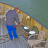Aboard the Friesland, the deckhand pulling the ropes in.