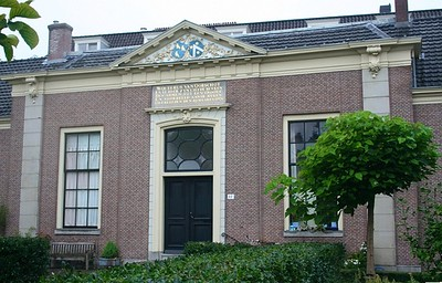 Wouterrus van Oorschot Building. On top of the main building you can see a triangle with sculptured coat of arms and other decorations. The Hofje is separated from the street by a wonderful monumental wrought iron gate with an entrance in Rococo Style.