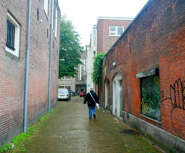 Leisbeth wandering down the back streets of Haarlem in the rain.  She holds a printout of our Haarlem tour in her hand.  The directions on the printout are sometimes difficult to understand.