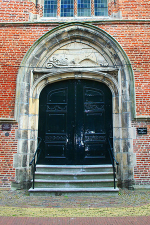 The Noorderkerk, also known Vrouwenkerk The centre door is in Empire style, dating from the early 19th C. The stone carving above, with the date 1647 shows a skeleton with a scythe, hourglass and ears of wheat and the words 'En Messem Immortalitatis' meaning 'see here the harvest of immortality'. In other words the comfortably off, worthy burger does not die but lives on in a changed form. We see him here as complete skeleton, reclining on a mat and supported with a cushion. The corn harvested with the scythe symbolises the harvest of immortality. The hour- glass is upright i.e. the sand (life) is still running through.  Many thanks to the guest who picked up my error - thank you so much.