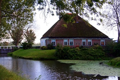 "Liesbeth drove through the village of Opperdoes on our way from Twisk to Medemblik.  I saw this georgeous house surrounded by water.  Opperdos is an old village in the Dutch province of North Holland.  It has a certain fame for its local variety of potatoes, ""Opperdoezer Ronde"".  In fact, the potatoes are so good that Liesbeth & Ed take a supply to Ed's Mum every weekend. The exact age of the village of Opperdoes is hard to determine. The village used to be located very close to the sea, and the area has been flooded several times. Initial settlements seem to have been abandoned after the year 300, because of large floods."