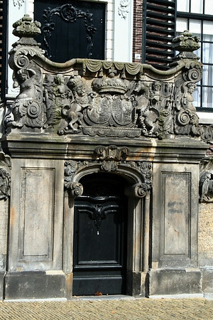 The entrance to the town hall is reached by a flight of steps, built in the years 1744-1745 and therefore older than the present facade. The steps are adorned by the coats-of-arms of Willem Karel Hendrik Friso, stadtholder of Friesland, and his spouse Anna van Brunswijk. The coats-of-arms were hacked out in 1795 (French revolution), but replaced in 1950. The town gaol was formerly located behind the door in the flight of steps.