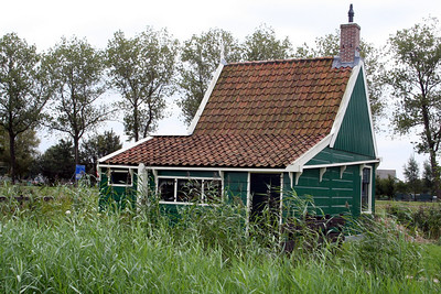 A typical gabled timber house in the village Zaanse Schans - with its traditional green painted houses, warehouses and windmills the Zaanse Schans gives the feeling of having stepped back into the seventeenth and eighteenth centuries, however this is not an open air museum but a colourful living and working neighbourhood. The hamlet has not always existed though. Most of the buildings were re-located from other areas in the Zaanstreek in the 1960's and 70's as owing to urban development they were under threat of obliteration. They were safely moved to the Zaanse Schans; the exact location where in 1574 Diederik van Sonoy, a Governor in the service of William of Orange, with the aid of local people, erected entrenchments or Schans to hold back the advancing Spanish army.