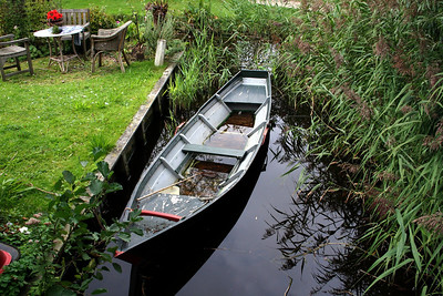 Boat in a canal beside a house