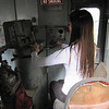 Jeannie sits in the engineer's chair.  The small window in front looks forward out over the diesel engine and generators.
