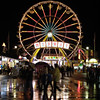 Rainy pavement captures neon reflections at a carnival midway. Motion blur on ferris wheel.