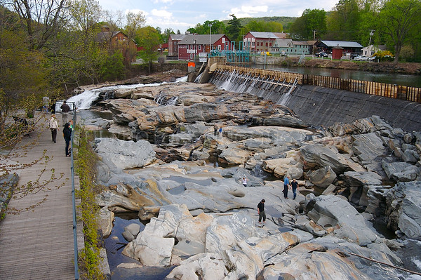 North America, USA, Massachusetts, Shelburne Falls. People explore the Glacial Potholes by the dam on Deerfield River in Shelburne Falls and others look on from an observation area