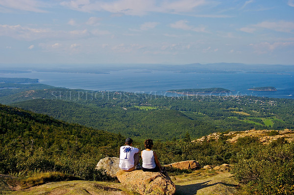 A man and woman sit on a rock on Cadillac Mountain overlooking the landscape and ocean, Acadia National Park, Maine