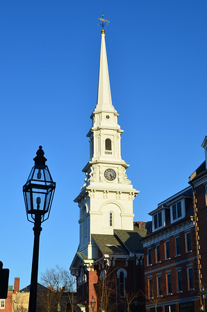 Street scene of Portsmouth, New Hampshire, featuring landmark church steeple and one of the city's many decorative lampposts.