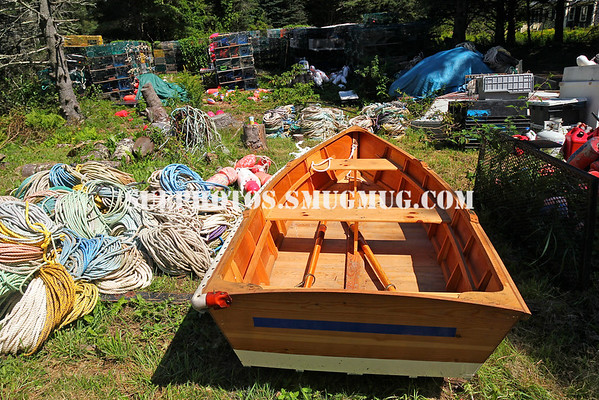 A rowboat, rope, and lobster traps amid trees on Monhegan Island, Maine