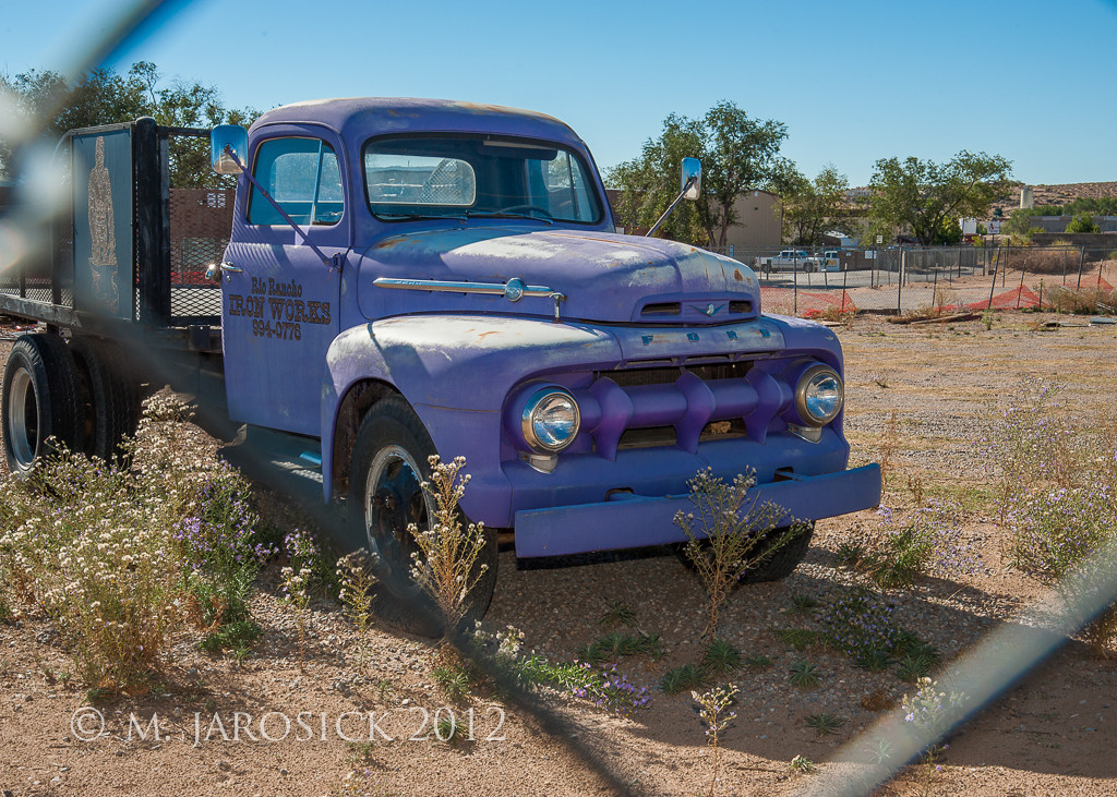 """Purple truck!  Mid-50's Ford survivor.  I was excited to find this opportunity to apply some of the lessons I learned in flash workshop (not the kind that requires a raincoat, but rather a Nikon SB-700).  The exposure was set to keep the bright sky and ground from being blown out and the flash illuminated the grill to keep the detail from being lost due to resulting gross underexposure.  Notice the """"catch light"""" in the headlights."""