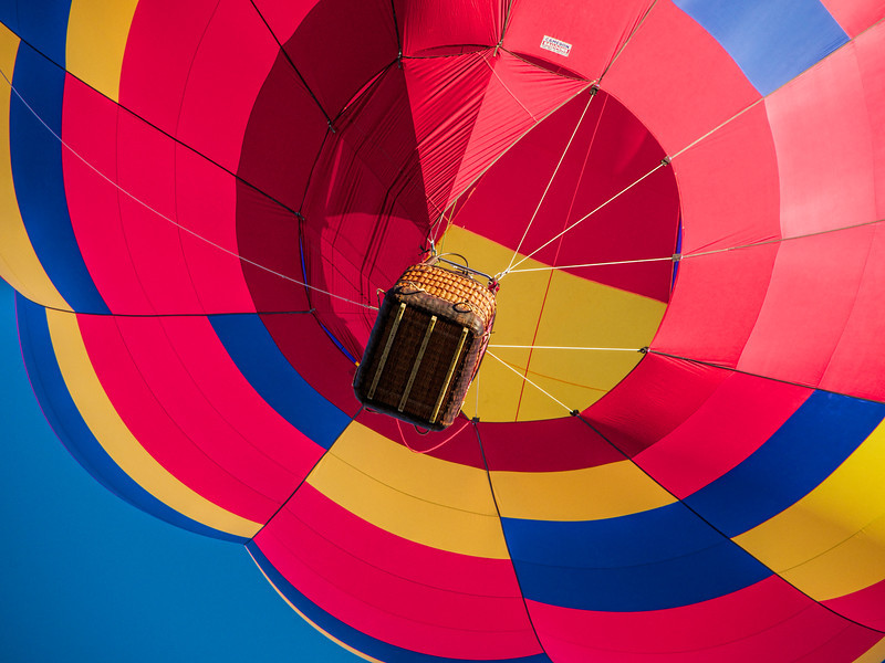 Underneath the basket of a balloon ascending over head.