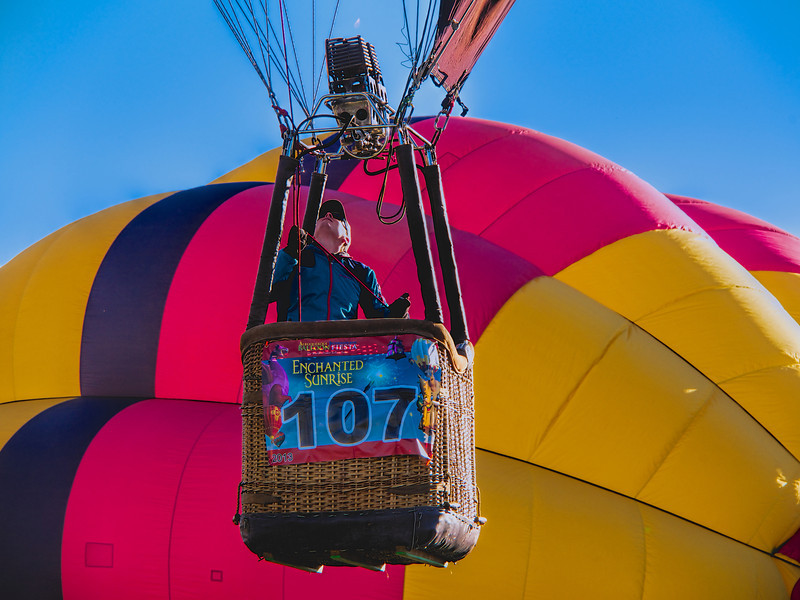 A solo rider in his basket, ascending next to another balloon still being inflated.