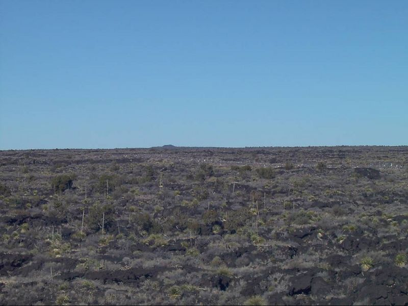 zg) The Valley of Fires is part of the El Malpais (Badlands). The small hill in the distance was the cinder cone (source) of this lava flow.