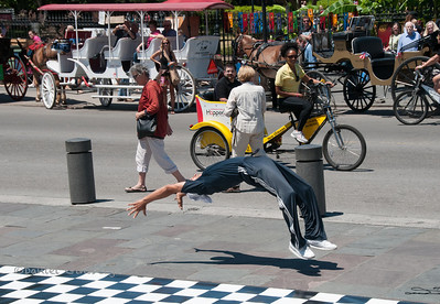 Street performer doing a back flip in front of Jackson Square in New Orleans.