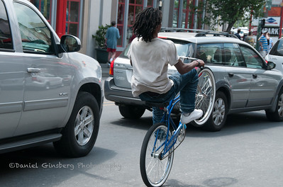 A bicyclist pops a wheelie on a street in New Orleans.
