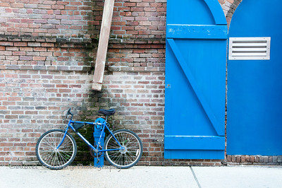 A blue bicycle leaning on a blue pipe coming out of a brick wall with a blue door to the side.
