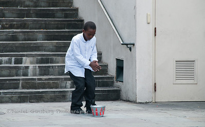 A boy tap dances on a New Orleans street with a Coca Cola decorated tip pail.