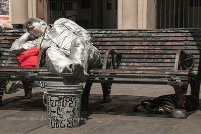 A silvered street performer seemingly sleeping on a bench, withhis dog underneath, in New Orleans.
