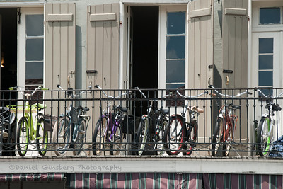 Bic;ycles of different colors on a balcony in New Orleans.