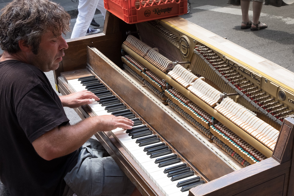 Another guy tickles the ivory on a battered piano set up on the street