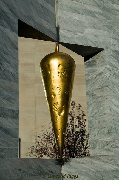 """East 2 West Source Point"" - a.k.a. ""Plumb Bob Brain"" - a Denver, Colorado outdoor streetside sculpture by Larry Kirkland. It is a two-sided ""Janus"" head, which is pierced by a square opening, in which hangs a golden plumb bob, a construction tool. Made in 2003 of carrera marble, cast bronze, and gold leaf, the sculpture is at the corner of Colfax Avenue and 14th Street."