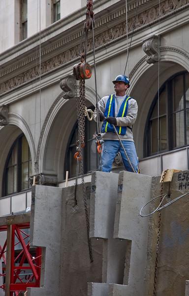 Attaching pre-fab concrete blocks to a crane hoist.