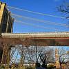 Brooklyn-side tower of Brooklyn Bridge with Manhattan Bridge viewable behind trees