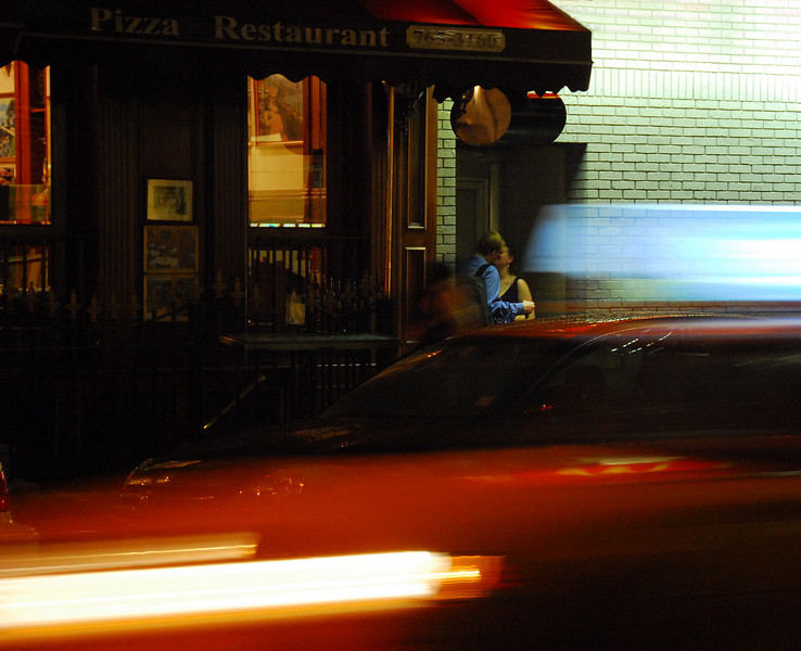 Meeting in the Doorway.<br /> The world rushes by, but time stops for the couple in the doorway?  <br /> The couple was there for maybe 20 minutes and it took a dozen trys to get a good image of them.