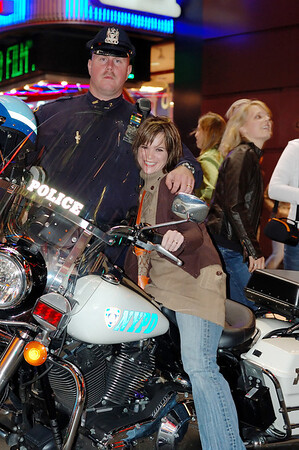 Emily posing on a NYPD's chopper.  Unfortunately this officer looks a bit too serious.