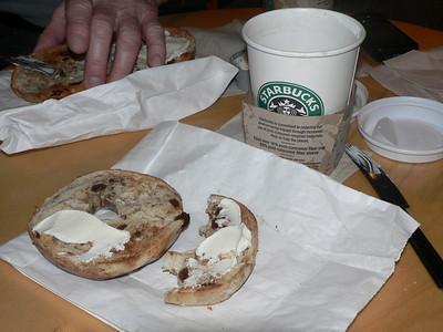 Kaffe americano och en rostad russinbagel med philadelfiaost