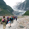 On valley floor, hikers and guides hiking to the glacier.