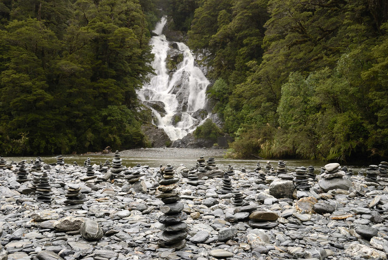 Haast Pass, falls and small stone cairns.