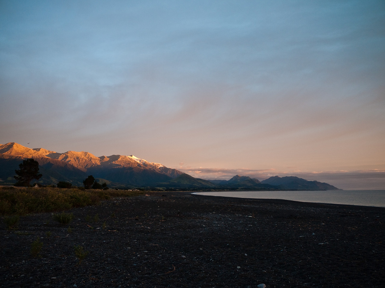 Sunlight descends on a snow-capped mountain peak on the coast at Kaikoura