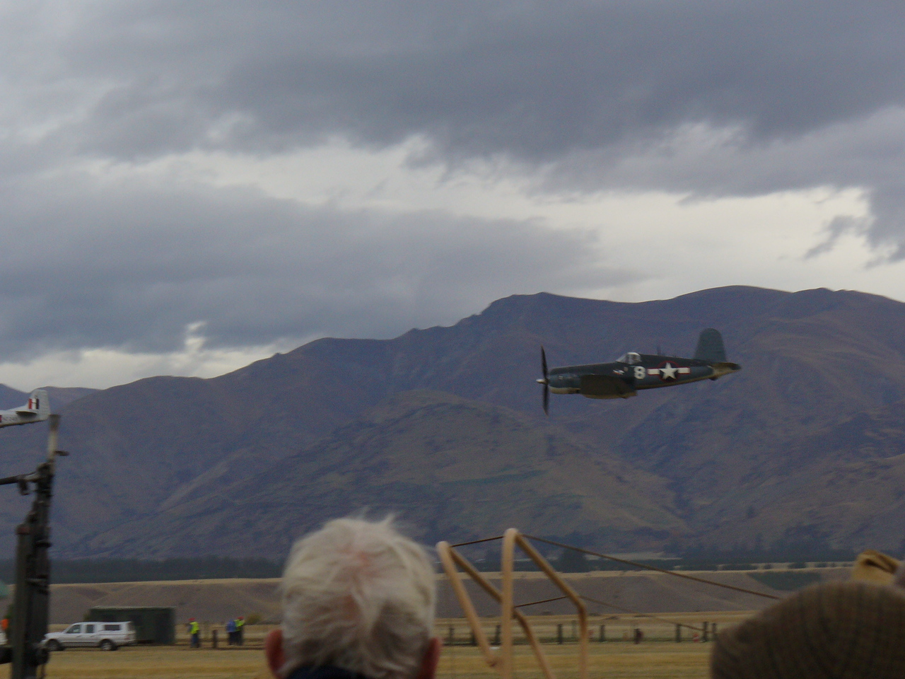 Poor photo of Corsair, tail of P-51 in front