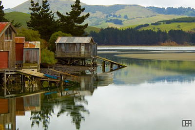 Weathered boat houses and still waters of the Papanui Inlet