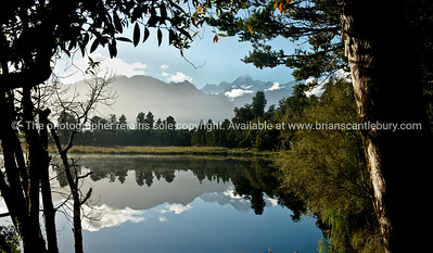 Lake Mathieson and the Southern Alps framed by native trees.