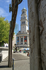 View through a Maori art installation towards the clock tower of the Town Hall in Auckland, New Zealand
