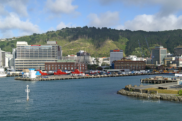 Arriving at the ferry pier in Wellington. Red tug boats and the Beehive can be seen in the background. Wellington, North Island, New Zealand