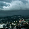 A view of Auckland from Sky Tower. You can see the extinct volcanoes in the background. Dark clouds and rain. It winter season in New Zealand.