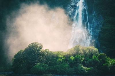 Waterfall and sun-lit spray, in fiord of Milford Sound