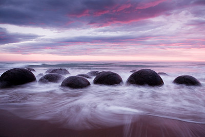 The Moeraki Boulders at sunrise.   The Moeraki Boulders are limestone rocks that formed as mineral deposits consolidated around a small piece of organic material. They can be as large as 3 meters in diameter.