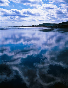 The clouds reflect perfectly on wet sand. Muriwai Beach, New Zealand (north island)