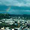 A view of Auckland from Sky Tower. You can see the extinct volcanoes in the background. It's winter time and a rain storm is coming through the area.... Not good for cameras, but great for rainbows.