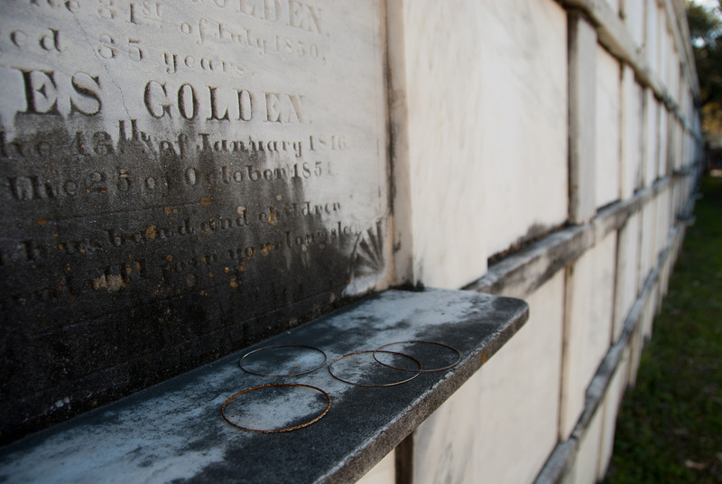 """<span id=""""title"""">Golden</span> <em>Lafayette Cemetery No. 1</em> This wasn't the only tomb where someone had left rings like these. The entire Northeast wall of the cemetery is like this - hundreds of crypts."""
