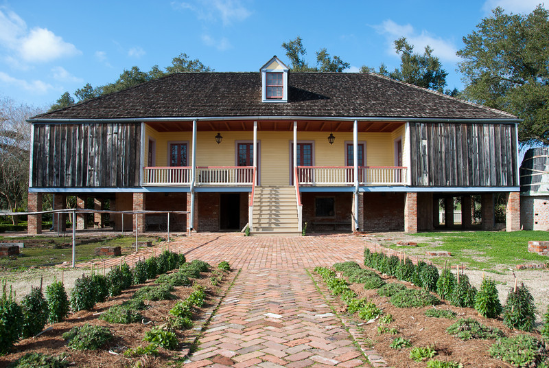 """<span id=""""title"""">Laura Plantation, Back</span> <em>Laura Plantation</em> Apparently the house used to have two wings on the side, making it a 'U' shape. Most of the house was recently rebuilt after an electrical fire. This was the original yellow color of the house, and that's one way you could distinguish the Creole plantations from the English ones - the Englishmen painted their houses white. After buying the run-down plantation property for tourism, the new owners discovered extensive memoirs written by Laura, so there were a lot of interesting stories about how things were done back then."""